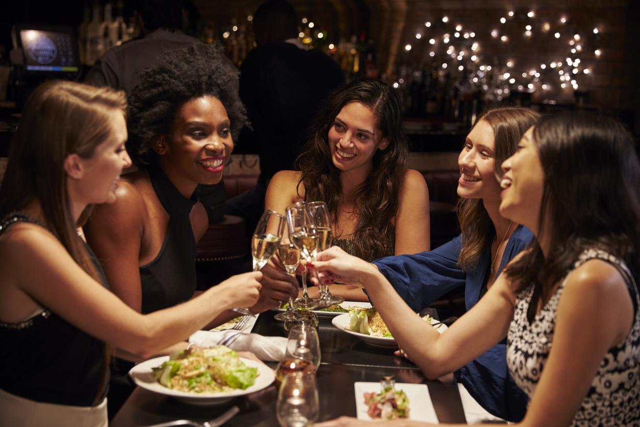 Group Of Female Friends Enjoying Meal In Restaurant for bridal shower